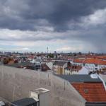 Das Foto zeigt die Dächer Berlins von Neukölln bis zum Fernsehturm bei starker dunkler Bewölkung.